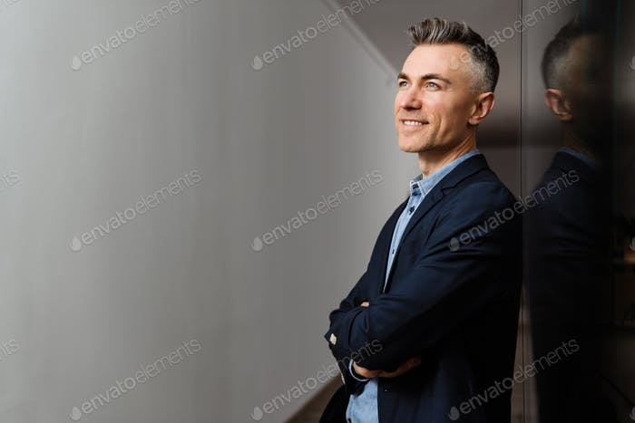 Happy grey man smiling and looking upward while leaning on wall