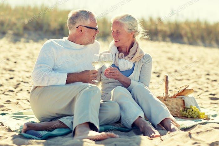 happy senior couple having picnic on summer beach