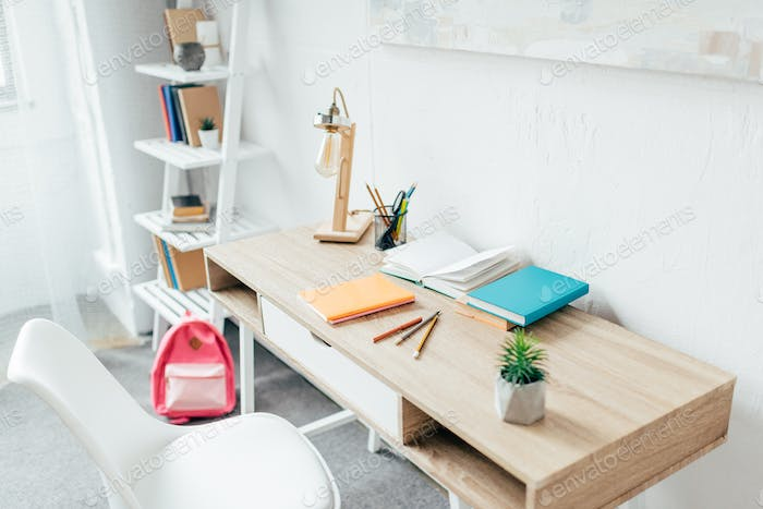 Minimalistic room interior with writing desk and school supplies placed on it.