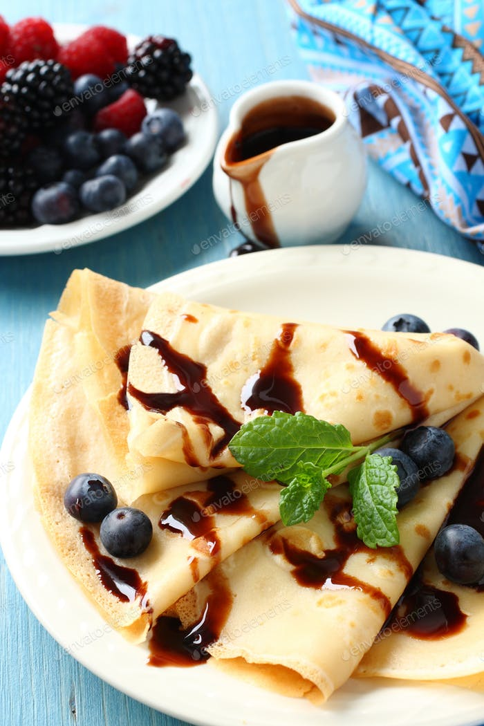 Homemade crepes with blueberries, chocolate sauce