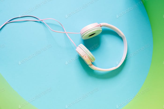 Overhead view of a pink wired headphones lying in the studio