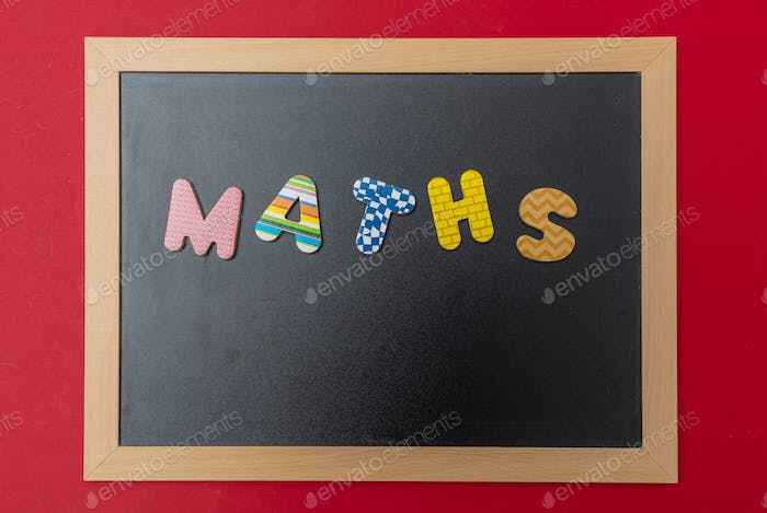 Black chalkboard with wooden frame, word, text maths in colorful letters, red wall background