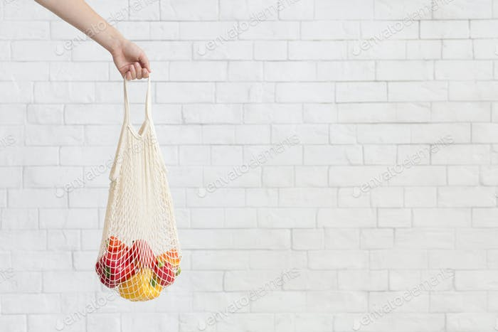 Woman holding Fresh paprika in Eco natural bag