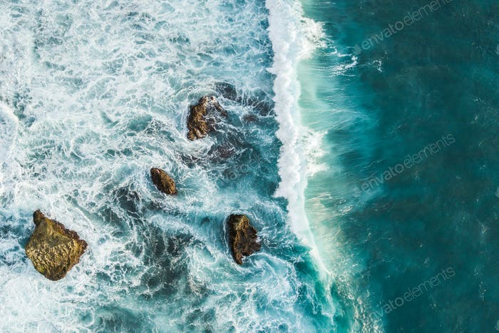Aerial view of crashing waves on rocks