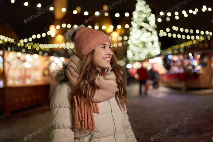happy young woman at christmas market in winter