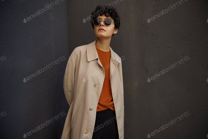 Fashionable young dark haired pretty female with short haircut standing over black urban wall