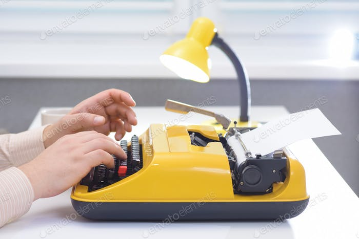 Man typing on yellow typewriter with lamp on white office desk near the window