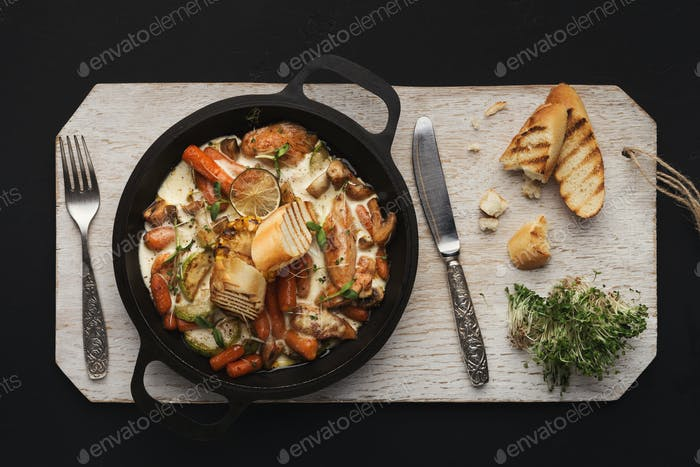 Meat and vegetable casserole on wooden board, top view