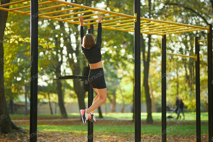 Mujer cruzando en barra horizontal durante la actividad al aire libre