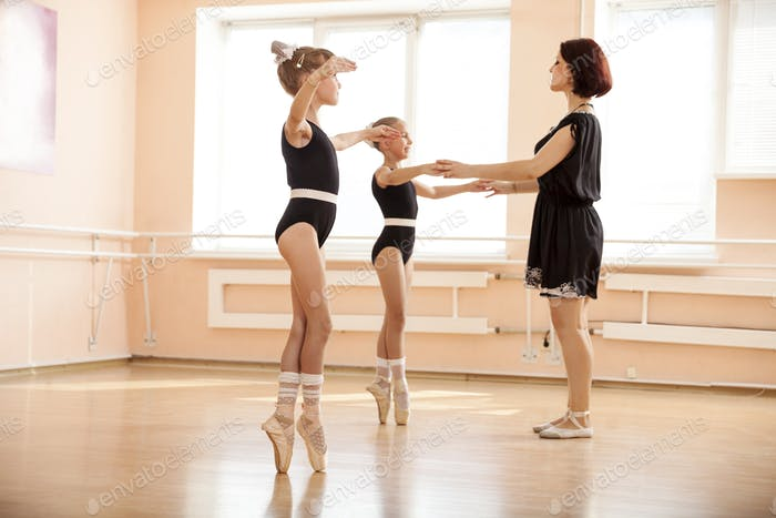 Ballet teacher helping young girls to dance en pointe