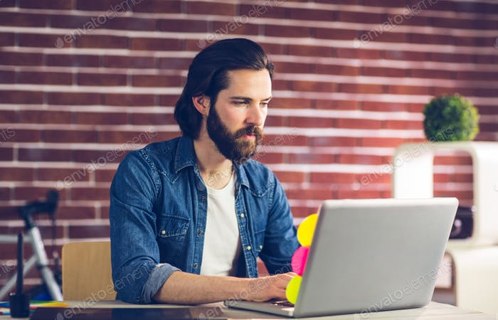 Confident businessman using laptop in creative office