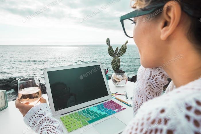 kostenlose digitale Nomade Frau bei der Arbeit mit einem Laptop im Freien Meerblick