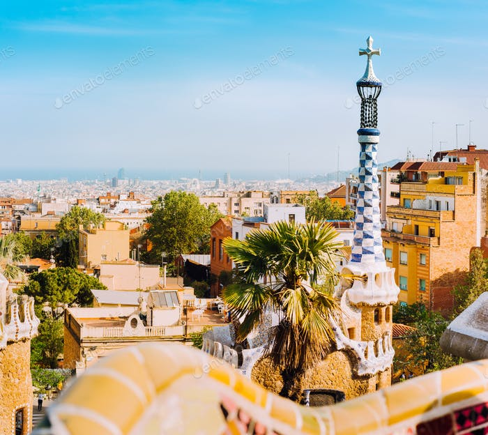 Porter lodge colorful tower and details of ceramic bench in Park Guell. Warm sunlight on rooftops