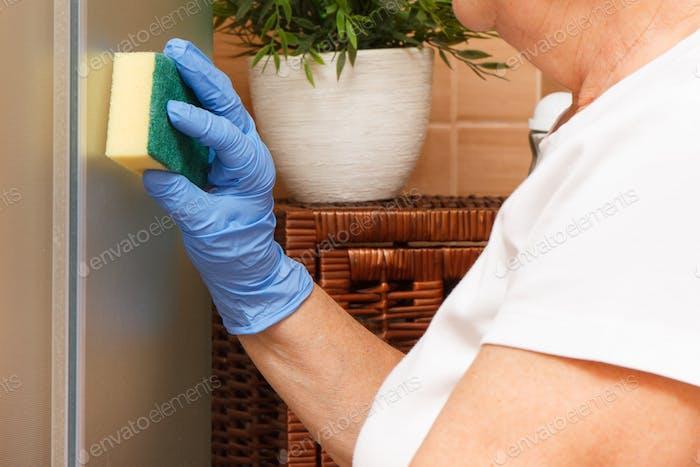 Hand von Senior Frau mit Schwamm und Wischglas Dusche Tür im Bad, Haushalt Pflichten Konzept