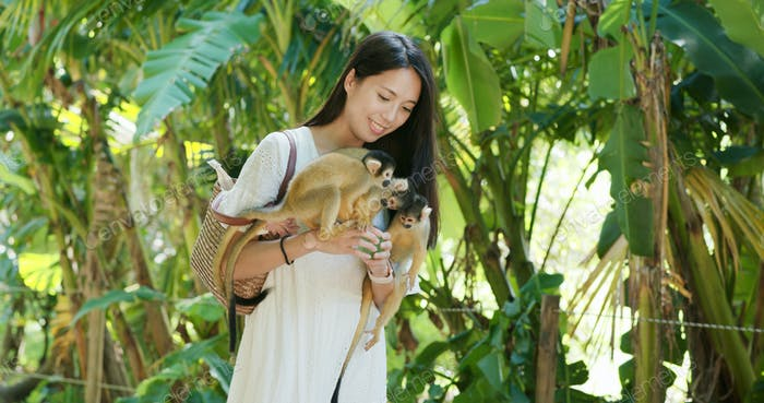 Woman tourist go to the park for visit  Squirrel Monkey