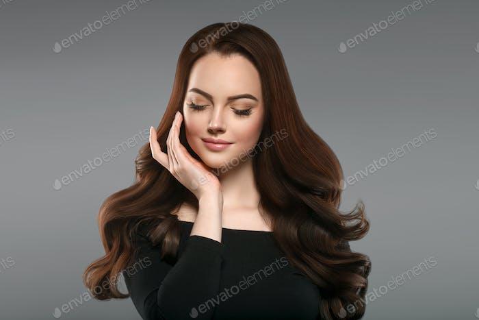 Brünett mit perfektem Haar. Frau schönes Porträt mit gesunden langen Frisur lockig und perfekt.