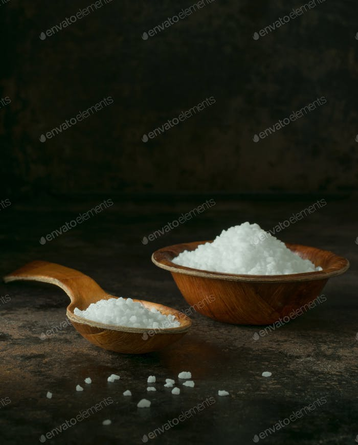A wooden spoon and bowl of salt crystals