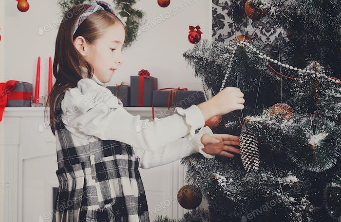 Hübsches kleines Mädchen schmücken großen Weihnachtsbaum
