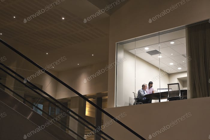 Conference room at night with two business people at work at a conference table.