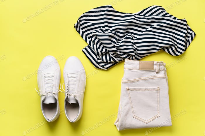 Female white sneakers and jeans, striped t-shirt on yellow background with copy space. Top view