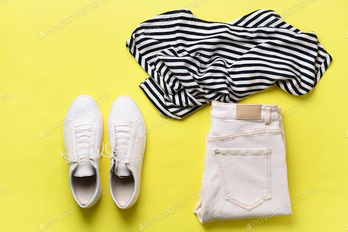 Weibliche weiße Turnschuhe und Jeans, gestreiftes T-Shirt auf gelbem Hintergrund mit Kopierraum. Ansicht von oben