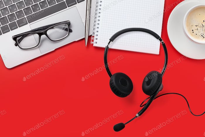 Office red workplace with coffee cup and headset