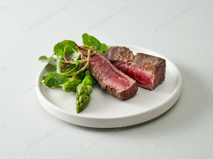 Plate of beef wagyu steak meat with herbs and asparagus