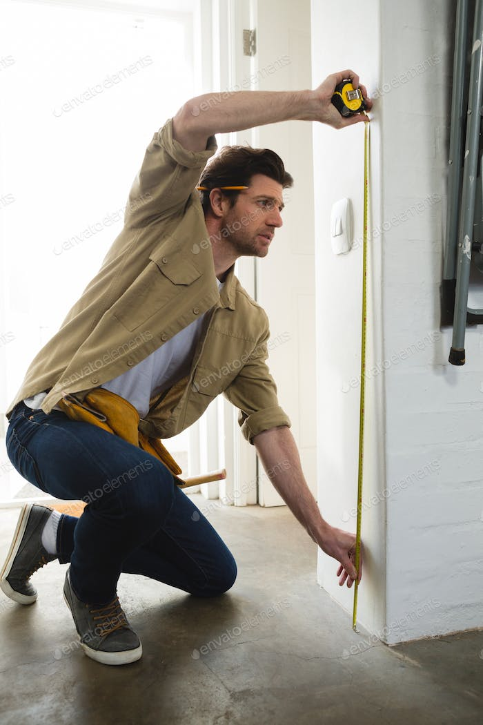 Male carpenter measuring a wall with measure tape