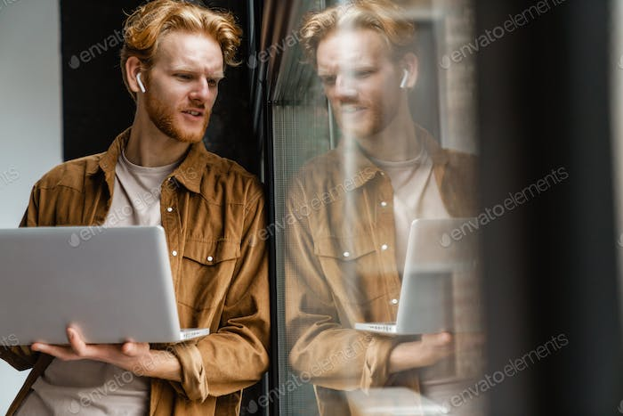 Brooding redhead guy in wireless earphones working with laptop