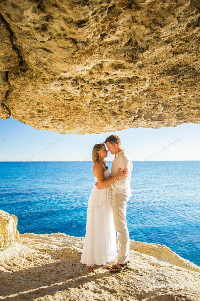 summer holidays, people, love and dating concept - happy couple hugging at summer sea background