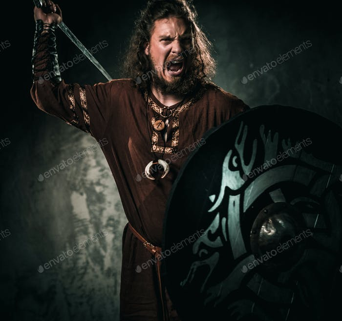 Furious viking with sword in a traditional warrior clothes