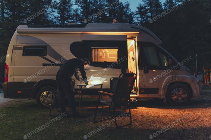 Men Browsing Local Map in Front of His RV