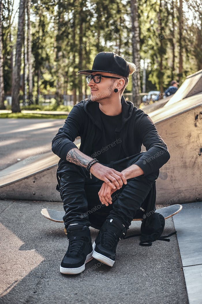 Stylish skateboarder in a black hoodie and cap sits on the board in the skatepark in the summer time