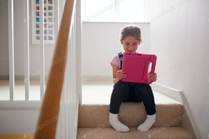 Girl Sitting On Stairs At Home Playing With Digital Tablet