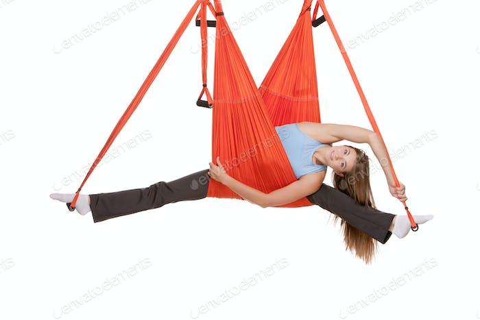 Junge Frau machen Antigravität Yoga-Übungen in Stretching Bindfäden