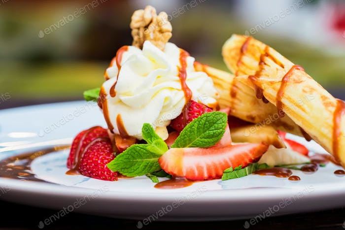 Close up delicious dessert with waffle rolls, ice cream and strawberries