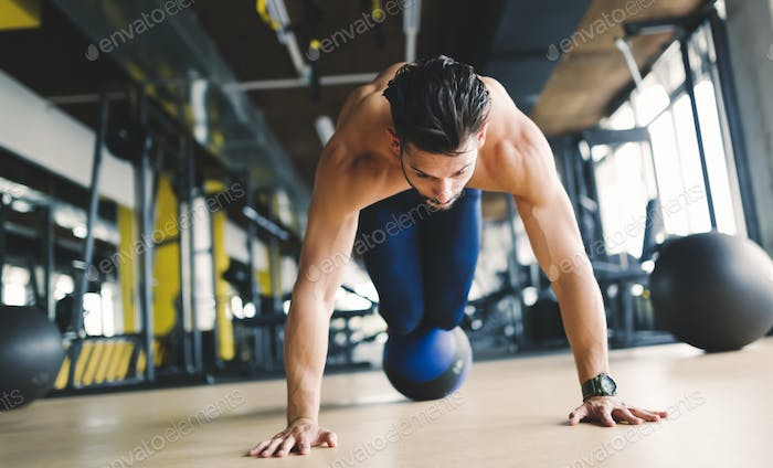 Sporty athlete doing push ups in gym