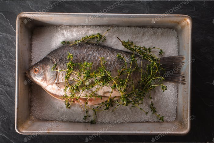 Raw crucian with salt and rosemary in baking dish