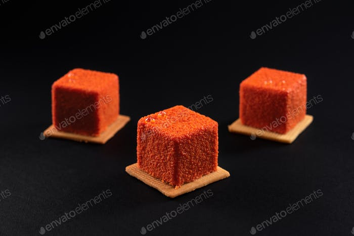 Orange square cakes with matte surface isolated on black