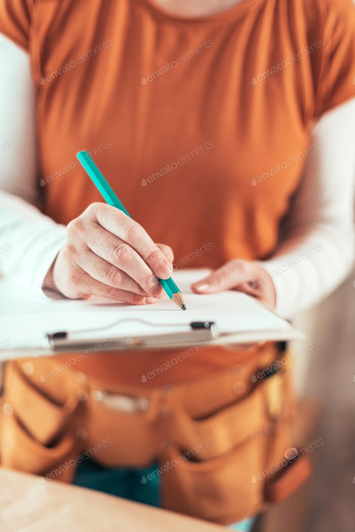 Self employed female carpenter writing project notes