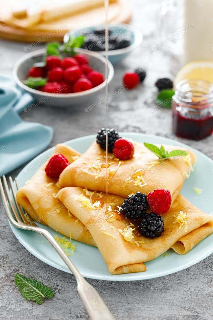Thin crepes with fresh berries and lemon zest. Pancakes with raspberry and blackberry.