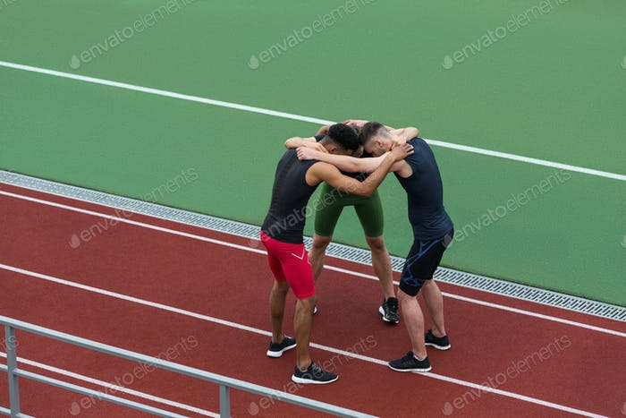 Schöne multiethnische Sportlermannschaft steht auf Laufbahn