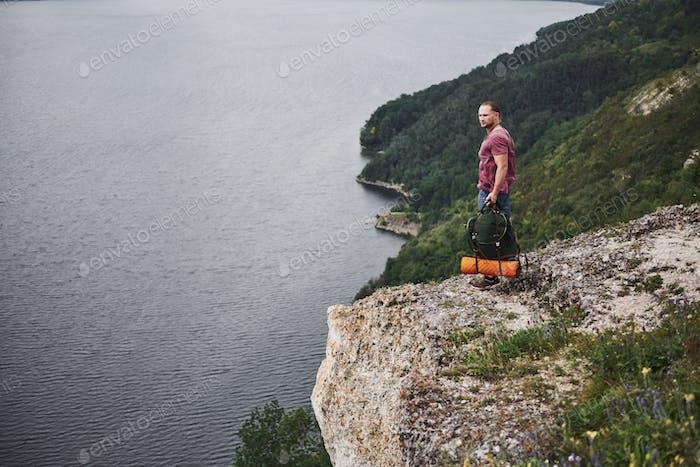 Attraktiver Mann, der den Blick auf die Bergwelt über der Wasseroberfläche genießt