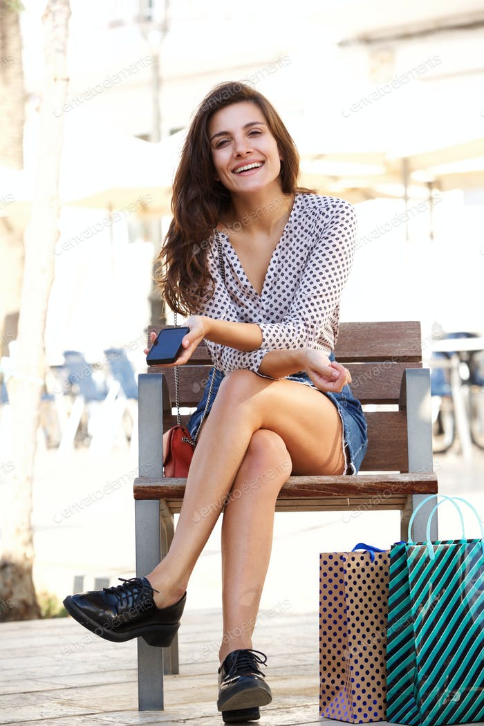 Full length happy woman sitting outside holding cellphone and shopping bags