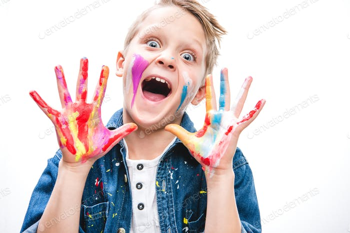 Excited schoolboy artist with painted face
