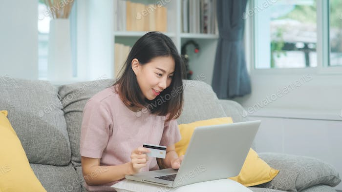 Asian woman using laptop and credit card shopping ecommerce, on sofa in living room at home.