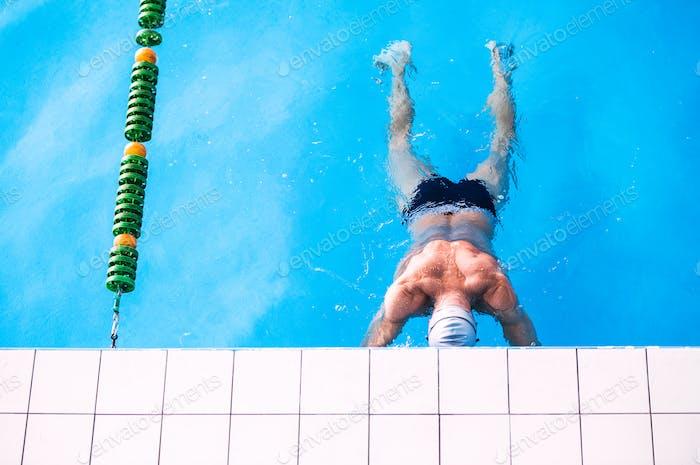 Senior man in an indoor swimming pool.
