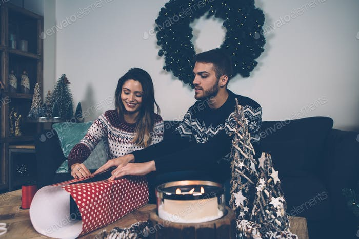 Front view of couple wrapping present together