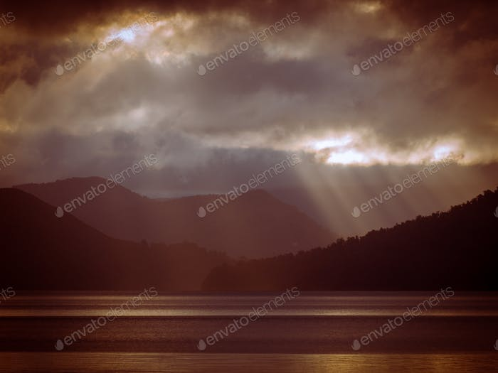 Sunrays shining through clouds over foggy mountain lake in vinta