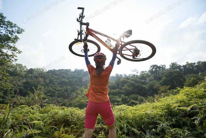 Successful woman biker lifting the bike to sunrise on mountain top